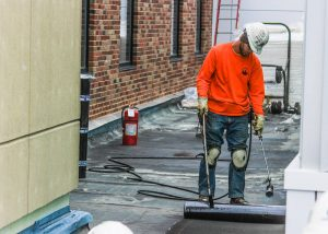 Roofer Installing Shingles during Commercial Roof Installation