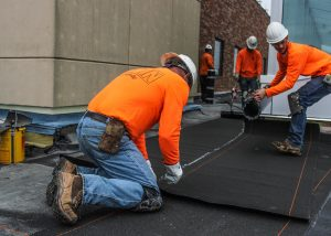 Roofers Installing Shingles during Commercial Roof Installation