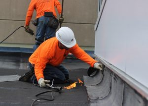 Roofer Using Torch to Heat Layers of Vinyl Roofing Shingles