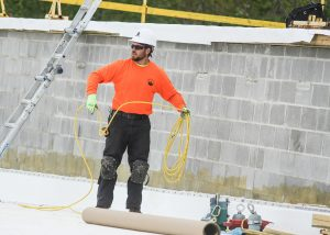 Roofer Winding a Yellow Safety Rope