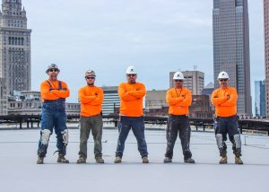 Roofers Standing Together with Arms Crossed on Commercial Job Site