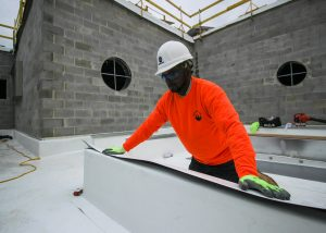 Roofer Gluing Materials During Roof Installation