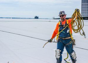 Roofer Gathering a Yellow Safety Rope
