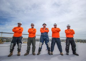 Roofers Standing Together with Arms Crossed on Roof