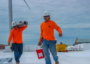 Roofers Carrying Materials on Commercial Job Site