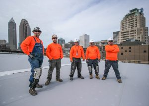 Roofers Standing Together on Commercial Job Site