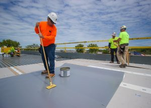 Roofer Spreading Layer of Vinyl Roofing