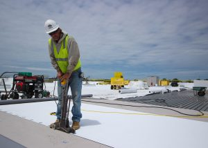 Roofer Drilling Rivets and Screws into Commercial Roof