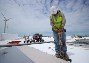 Roofer Drilling Rivets on Roof