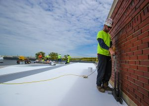 Roofer Drilling Rivets and Screws on Commercial Roof